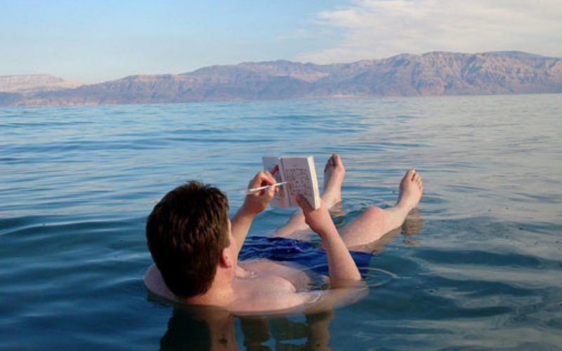 man-reading-book-while-floating-in-dead-sea