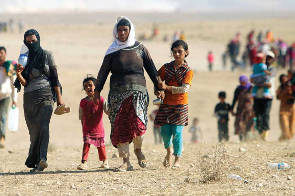 Displaced people from the minority Yazidi sect, fleeing violence from forces loyal to ISIS in the town of Sinjar, walk toward the Syrian border on Aug. 11, 2014. Photo by Rodi Said/ Reuters